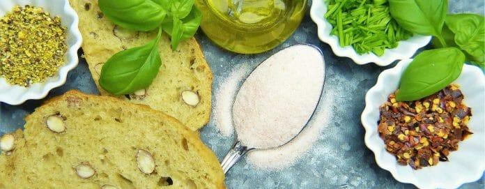 Guarkernmehl: Löffel mit Mehl zwischen Brot, Öl und Kräutern.